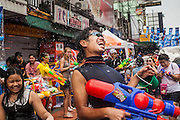 13 APRIL 2014 - BANGKOK, THAILAND: A tourist gets hit in the back with ice cold water during a water fight on Khao San Road, Bangkok's backpacker district on the first day of Songkran. Songkran is celebrated in Thailand as the traditional New Year's Day from 13 to 16 April. Songkran is in the hottest time of the year in Thailand, at the end of the dry season and provides an excuse for people to cool off in friendly water fights that take place throughout the country. Songkran has been a national holiday since 1940, when Thailand moved the first day of the year to January 1.     PHOTO BY JACK KURTZ