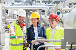 Engineer with his colleagues in meeting and showing something at geothermal power station, Bavaria, Germany