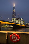 The Shard skyscraper, London Bridge and a life ring overlooking the Thames river on a winter's evening, on 23rd November 2018, in London, England.