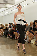 Black calf-length pants and strapless white peplum belted top. By Carmen Marc Valvo at the Spring 2013 Fashion Week show in New York.