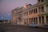 American car and buildings along the Malecon at dusk, Havana, Cuba