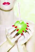 beautiful caucasian woman portrait offering apple studio on green background