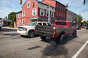 A pickup truck expels black smoke as it passes demonstrators at the Mifflinburg Pride Event.