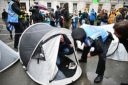 © Licensed to London News Pictures. 08/10/2019. London, UK. Police remove Extinction Rebellion tents on Whitehall, outside Downing Street. Activists have converged on Westminster for a second day, blockading roads in the area and calling on government departments to 'Tell the Truth' about what they are doing to tackle the Emergency. Photo credit: Ben Cawthra/LNP