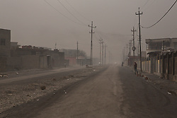 Licensed to London News Pictures. 08/11/2016. Qayyarah, Iraq. A deserted smog filled street, close to burning oil facilities, is seen in the Iraqi town of Qayyarah. Oil wells in and around the town of Qayyarah, Iraq, we set alight in July 2016 by Islamic State extremists as the Iraqi military began an offensive to liberated the town.<br /> <br /> For two months the residents of the town have lived under an almost constant smoke cloud, the only respite coming when the wind changes. Those in the town, despite having been freed from ISIS occupation, now live with little power, a water supply tainted with oil that only comes on periodically and an oppressive cloud of smoke that coats everything with thick soot. Many complain of respiratory problems, but the long term health implications for the men, women and children living in the town have yet to be seen. Photo credit: Matt Cetti-Roberts/LNP