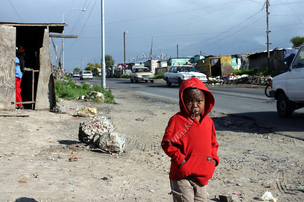 Thulani, 5, a HIV positive child living in Philippe township, Cape Town, is standing on the side of the road. He is living with his mother and relatives in a small wooden shack.