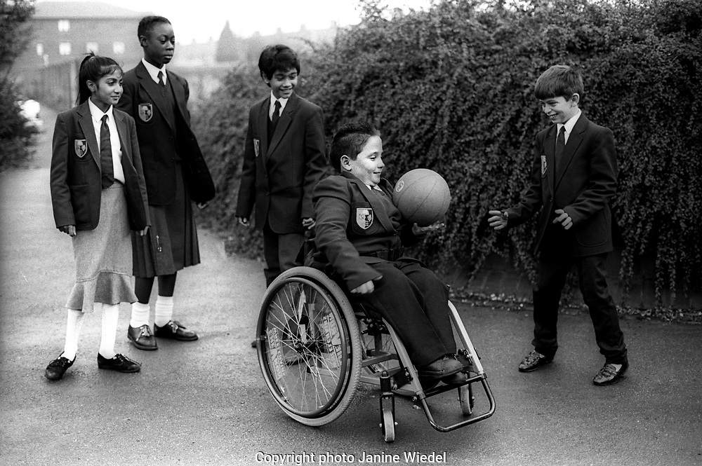 Physically disables boy in wheelchair  plays ball games at break time in the school yard.
