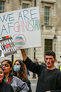 """An Afghan man carries a placard that reads """"We are Afghanistan"""" during a protest """"Save Afghanistan"""" to protest the resurgence of the Taliban outside Downing Street, Britain's PM Office in central London on Saturday, Aug 21, 2021. (VX Photo/ Vudi Xhymshiti)"""