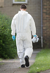 © Licensed to London News Pictures. 26/05/2018. Crawley, UK. A police forensics officer walks towards a block of flats in Crawley where a woman was found dead.  A man has been arrested on suspicion of murder after the woman was found in her bed. Police are appealing for witnesses to come forward.  Photo credit: Peter Macdiarmid/LNP