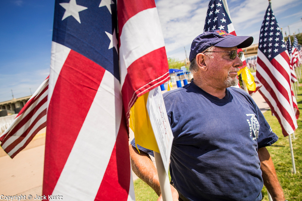 10 SEPTEMBER 2012 - TEMPE, AZ:     JOHN SERIO, a retired Denver, CO, firefighter who worked at Ground Zero after the September 11, 2001, attacks, walks through the Healing Field in Tempe, AZ, Monday. The Exchange Club of Tempe and the city of Tempe are hosting the 9th Annual Healing Field display. The annual event posts three thousand American flags in the Tempe Beach Park. The flags are 3?X5?  and stand 8? tall. The display is a tribute to those who died in the terrorist attacks of September 11, 2001. Nearly 3,000 people were killed when terrorists affiliated Al-Qaeda crashed commercial airliners into the World Trade Center in New York, the Pentagon in Arlington, VA, and a field in Ohio.   PHOTO BY JACK KURTZ