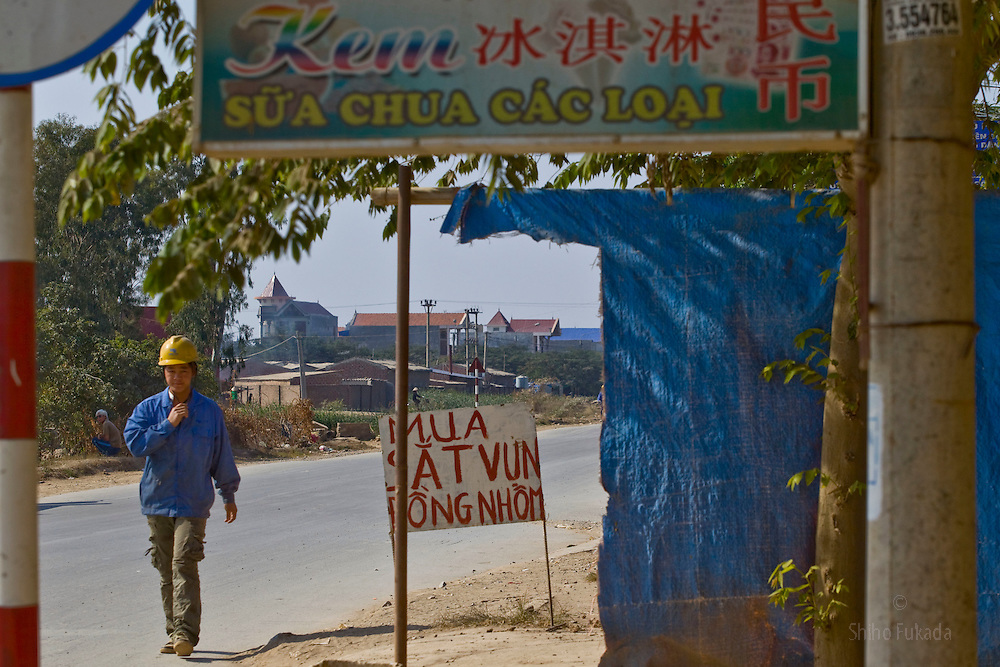 A worker walks nearby a Vietnamese and Chinese sign near the Haiphong Thermal Power Plant construction site in Trung Son, Vietnam, Nov. 22, 2009. At the construction site here, a few miles northeast of the port city of Haiphong, an entire Chinese world has sprung up, including four walled dormitory compounds for the Chinese workers, restaurants with Chinese signs advertising dumplings and fried rice, and currency exchange shops.