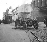 1304E-1. An automobile caught fire and is blocking the tracks of the Mt. Tabor trolley downtown on SW Morrison where the tracks curve to turn north on 3rd Avenue. On the right is Baron's Shoe Store at 230 Morrison. 1918