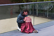 Homeless man holds a sign begging on Millennium Bridge near to Tate Modern, London. This is a regular spot for homeless to ask fror money.