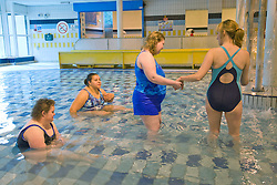 Day Service officer and Care assistant supervising two women day service users with learning disabilities at a swimming session at the local swimming pool,