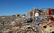 A resident removes debris from a tornado-destroyed house in Oklahoma City, Oklahoma May 22, 2013.  Rescue workers with sniffer dogs picked through the ruins on Wednesday to ensure no survivors remained buried after a deadly tornado left thousands homeless and trying to salvage what was left of their belongings.  REUTERS/Rick Wilking (UNITED STATES)