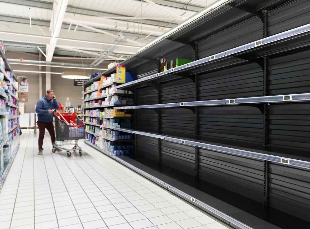 L'Intermarché de La Loupe, le 18 mars 2020<br /> Un client fait ses courses au supermarché, devant les rayons de papiers toilettes entièrement vides.