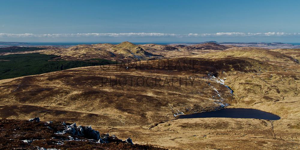 On the slopes of Sgarbh Breac this is the view towards Giùr-bheinn's distinctive ridge. The Bunnahabhain forest and Loch Mihurchaidh also visible