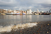 A wave breaks on the beach at low tide on the River Thames, with St Paul's Cathedral in the background. The South Bank is a significant arts and entertainment district, and home to an endless list of activities for Londoners, visitors and tourists alike.