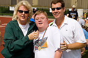 Parents pose with athlete son after winning medal. Special Olympics U of M Bierman Athletic Complex. Minneapolis Minnesota USA