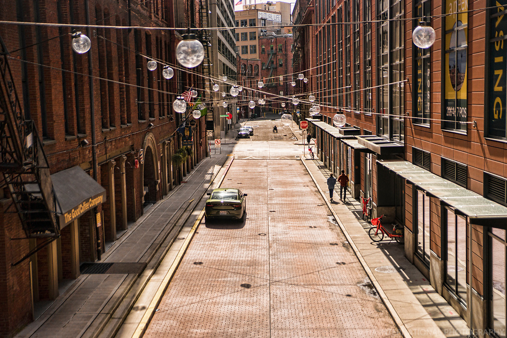 A couple strolls on the sidewalk along the decorative, quaint, narrow, and very empty Post Avenue in Downtown Seattle. (April 4, 2020).