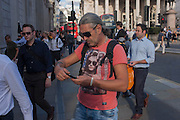 A man with sunglasses in a t-shirt featuring a woman in shades, checks his phone in the City of London, England UK.