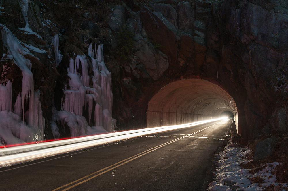 A car drives through Marys Rock Tunnel along Skyline Drive in Shenandoah National Park in wintertime.