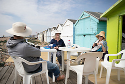 © Licensed to London News Pictures. 22/04/2019. Lancing, UK. People sit outside their beach hut to enjoy the warm weather in Lancing, West Sussex as most of the UK enjoys record breaking high temperatures over the Easter weekend. Photo credit: Peter Macdiarmid/LNP