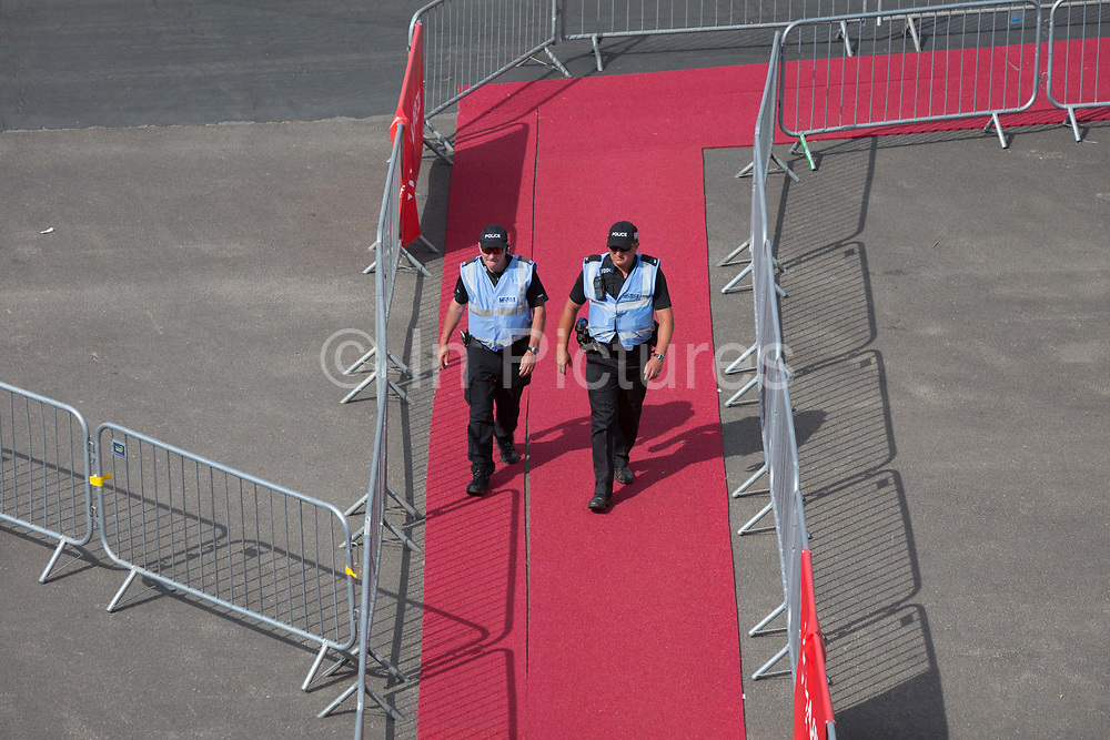Police officers patrol a red carpet at the Leonardo formerly Finmeccanica exhibition stand at the Farnborough Airshow, on 16th July 2018, in Farnborough, England.