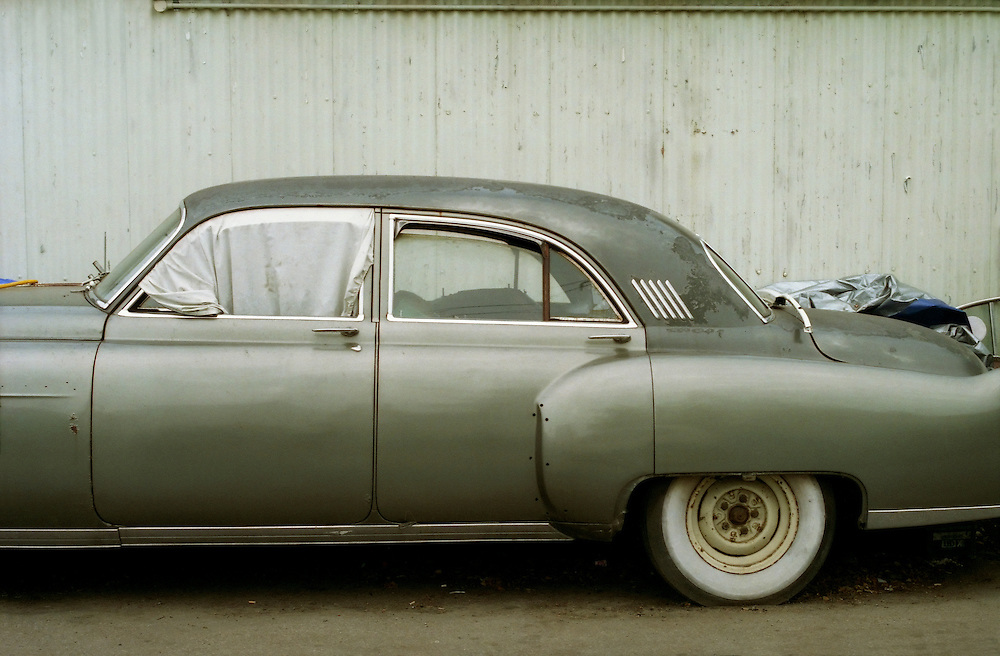 A vintage car in the process of refurbishment at an auto shop.