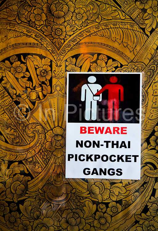 Warning sign for thieves in Wat Pho temple, Bangkok. Wat Pho is one of the largest and oldest wats in Bangkok (with an area of 50 rai, 80,000 square metres), and is home to more than one thousand Buddha images, as well as one of the largest single Buddha images of 160ft length: the Reclining Buddha .
