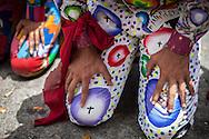 Los diablos pagan promesa al Santísimo andando de rodillas sobre el piso caliente durante la festividad del Corpus Christi, representada en Venezuela a traves del ritual magico-religioso de los Diablos Danzantes. Los Diablos de Naiguata se identifican por pintar sus propios trajes y decorarlos con cruces, rayas y circulos, figuras que impiden que el maligno los domine. Las mascaras son en su gran mayoria animales marinos. Llevan escapularios cruzados, crucifijos y cruces de palma bendita. Naiguata, 30 Mayo 2013. (ivan gonzalez)