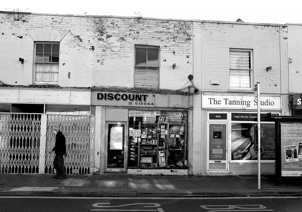A man wearing a face covering walks past temporarily closed shops on Cheltenham High Street on November 5, 2020 as England enters its second lockdown following a rise in COVID-19 cases. All non-essential shops are closed with supermarkets and builders' merchants remaining open.