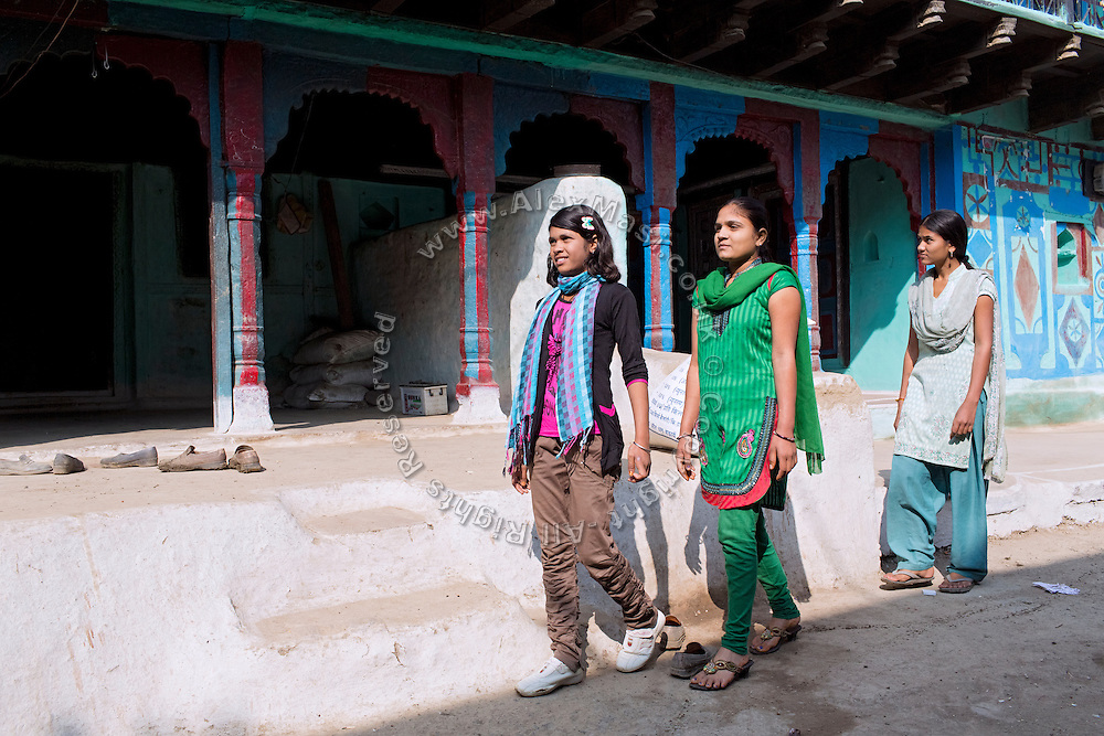 Ritu Gaur, 13, (left) is walking with her older sister, Malti, 17, (centre) and her younger sister, Shalu, 12, (right) on a road of her village, Chittawaliya, in rural Sehore, Madhya Pradesh, India. Ritu lives in the Jamoniya Tank Girls Hostel where the Unicef India Sport For Development Project has started in 2012. Covering 313 state-run girls' hostels and 207 mixed hostels in Madhya Pradesh, the project ensures that children from Scheduled Tribes (ST) and others amongst the poorest people in India, can easily access education and be introduced to sports. Field workers from Unicef also oversee their nutrition and monitor the overall conditions of each pupil.