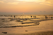 Groups of people swimming in the Bay of Bengal sea during sunset on Laboni Beach, Cox Bazar, Chittagong Division, Bangladesh, Asia. The sun is setting behind clouds in the sky and the horizon is warm with an orange glow.
