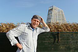 Farmer with tractor in his cornfield, geothermal power station in background, Bavaria, Germany