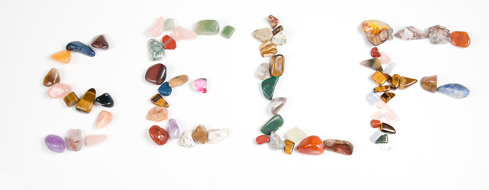New age crystals and gemstones spelling out Self