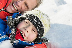 Father and son having fun in snow, smiling, portrait, Bavaria, Germany