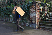 Man carries a piece of furniture on his shoulder echoing the brick pattern on an Edwardian park wall in south London