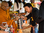 26 DECEMBER 2014 - MAE KHAO, PHUKET, THAILAND: People present food and offerings to Buddhist monks during a memorial service at the Tsunami Memorial Wall in Mae Khao, Phuket. The wall is located at the site that was used as the main morgue for people killed in the tsunami and hosts an annual memorial service. Nearly 5400 people died on Thailand's Andaman during the 2004 Indian Ocean Tsunami that was spawned by an undersea earthquake off the Indonesian coast on Dec 26, 2004. In Thailand, many of the dead were tourists from Europe. More than 250,000 people were killed throughout the region, from Thailand to Kenya. There are memorial services across the Thai Andaman coast this weekend.    PHOTO BY JACK KURTZ