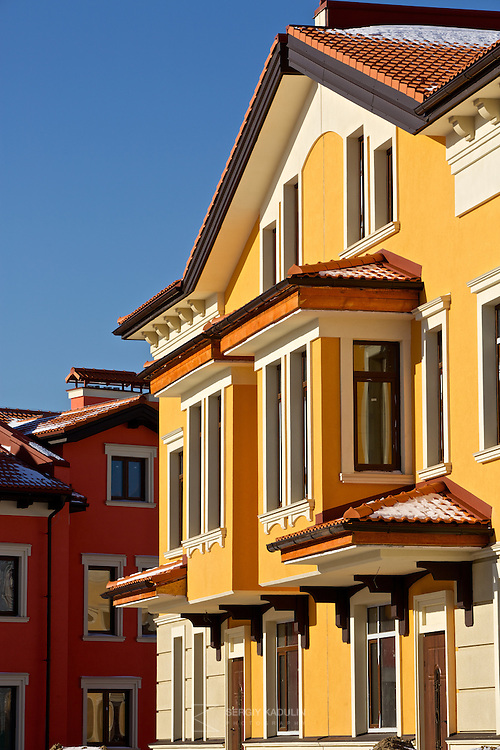 """Architectural details of residential real estate development project """"Italian Village"""" in Kyiv, Ukraine. Exterior view of villeta with yellow walls in the sunset sunlight."""