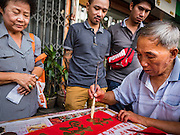 "18 JANUARY 2017 - BANGKOK, THAILAND: People watch a traditional Chinese calligrapher write out New Years greetings in Bangkok's Chinatown district, before the celebration of the Lunar New Year. Chinese New Year, also called Lunar New Year or Tet (in Vietnamese communities) starts Saturday, 28 January. The coming year will be the ""Year of the Rooster."" Thailand has the largest overseas Chinese population in the world; about 14 percent of Thais are of Chinese ancestry and some Chinese holidays, especially Chinese New Year, are widely celebrated in Thailand.       PHOTO BY JACK KURTZ"
