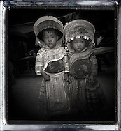 Portrait of two young Hmong boys wearing ethnic clothes and headgear.