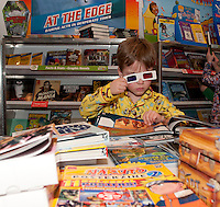6 year old Andrew Hosmer goes over the edge 3D style with a Star Wars book from the Holy Trinity book fair Tuesday evening followed by milk and cookies.  (Karen Bobotas/for the Laconia Daily Sun)
