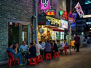 SEOUL, SOUTH KOREA: Men sit outside and eat at a Korean barbecue shop in Seoul.       PHOTO BY JACK KURTZ