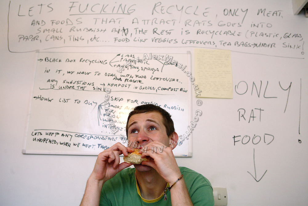 Zil, 23, from Poland, is having a sandwich in the kitchen of the Wildwood Road mansion while notes have being written on a board behind his back on how to deal with various issues concerning the newly entered house, on Thursday, June 28, 2007, in Hampstead, London, England. Situated opposite Hampstead Heath, North London's green jewel the average price for properties on this road reaches £ 2,500,000. Million Dollar Squatters is a documentary project in the lives of a peculiar group of squatters residing in three multi-million mansions in one of the classiest residential neighbourhoods of London, Hampstead Garden. The squatters' enthusiasm, their constant efforts to look after what has become their home, their ingenuity and adventurous spirit have all inspired me throughout the days and nights spent at their side. Between the fantasy world of exclusive Britain and the reality of squatting in London, I have been a witness to their unique story. While more than 100.000 properties in London still lay empty to this day, squatting provides a valid, and lawful alternative to paying Europe's most expensive rent prices, as well as offering the challenge of an adventurous lifestyle in the capital.