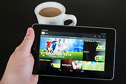 Man holding  Google Nexus tablet computer running android operating system and looking at Google Play Store screen