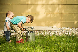 Two little boys in the garden filling watering can