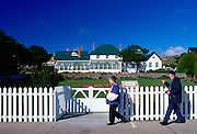 People walking past Government House in Port Stanley, Falkland Islands