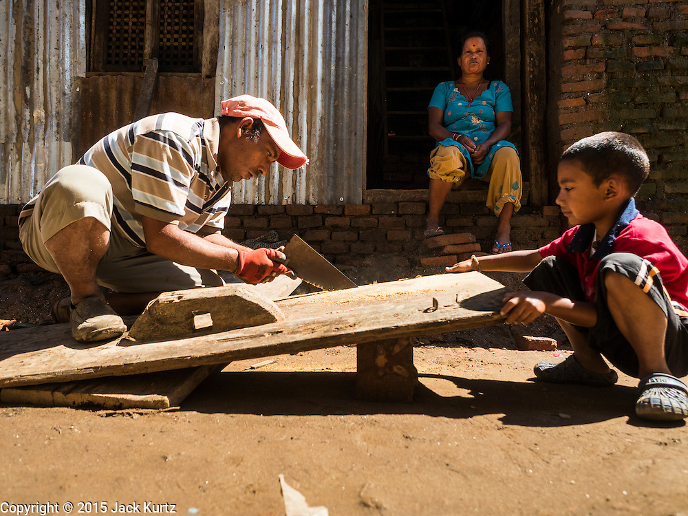 03 AUGUST 2015 - SANKHU, NEPAL: A man and his son repair the doors to their home in Sankhu, a community about 90 minutes from central Kathmandu. He is a farmer who works on his home when he has time in between tending to his fields. His family is living in the home while they work on it. The Nepal Earthquake on April 25, 2015, (also known as the Gorkha earthquake) killed more than 9,000 people and injured more than 23,000. It had a magnitude of 7.8. The epicenter was east of the district of Lamjung, and its hypocenter was at a depth of approximately 15km (9.3mi). It was the worst natural disaster to strike Nepal since the 1934 Nepal–Bihar earthquake. The earthquake triggered an avalanche on Mount Everest, killing at least 19. The earthquake also set off an avalanche in the Langtang valley, where 250 people were reported missing. Hundreds of thousands of people were made homeless with entire villages flattened across many districts of the country. Centuries-old buildings were destroyed at UNESCO World Heritage sites in the Kathmandu Valley, including some at the Kathmandu Durbar Square, the Patan Durbar Squar, the Bhaktapur Durbar Square, the Changu Narayan Temple and the Swayambhunath Stupa. Geophysicists and other experts had warned for decades that Nepal was vulnerable to a deadly earthquake, particularly because of its geology, urbanization, and architecture.    PHOTO BY JACK KURTZ