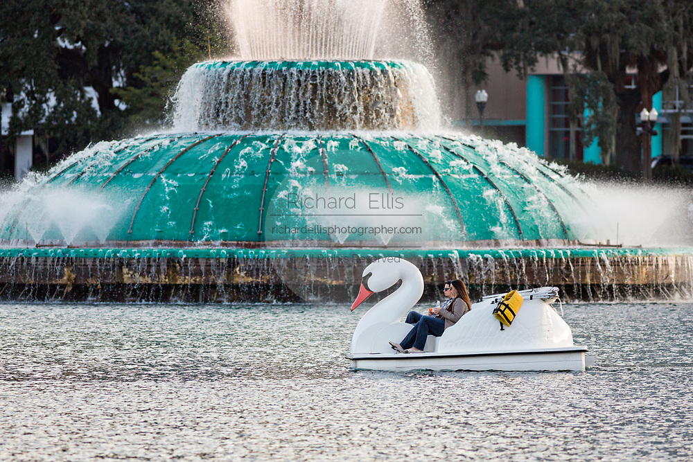 Tourists paddle Swan boats around Lake Eola Park past the Linton E. Allen Memorial Fountain in Orlando, Florida. Lake Eola Park is located in the heart of Downtown Orlando and home to the Walt Disney Amphitheater.